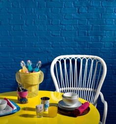 Bright blue brick work contrasts beautifully with the eye-catching yellow table