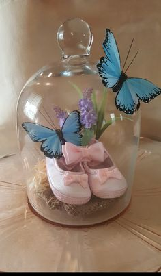 Girl baby shower decoration. Infant shoes under glass. I created this for my daughter's baby shower. I added the butterflies and plant (fake, of course). The shoes were part of a shoe and headband set, I used the headband as an additional way to keep the shoes tight together. I got the shoes/ headband from Wal-Mart, the butterflies and plant from the dollar tree. The plate and glass were a loan from my mother-in-law. Girl Baby Shower Decorations, Baby Girl Shower Themes, Baby Shower Centerpieces, Baby Shower Parties, Baby Shower Princess, Baby Shower Gender Reveal, Butterfly Baby Shower, Baby Shower Flowers, Butterfly Theme Party