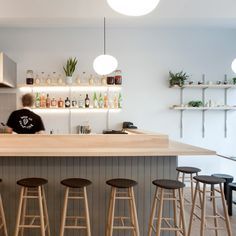 Architect Giles Reid has paired wooden furniture with bulbous lighting and pastel-coloured crockery to create a Japanese restaurant in Dalston, east London
