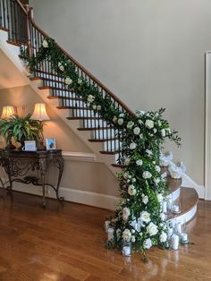 Greenery and florals trailing up staircase at home wedding.