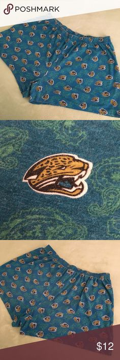 """NFL Jacksonville Jaguars logos teal sleep shorts GUC NFL 100% cotton """"tee shirt"""" fabric teal Jacksonville Jaguars sleep shorts from early 2000s. Fabric pattern is covered with gold, teal, black, and white Jaguar head logos in a random pattern along with green paisley designs. Pajama style elastic waist and 1 button fly closure. NFL Jacksonville Jaguars logos teal sleep shorts. NFL Shorts"""