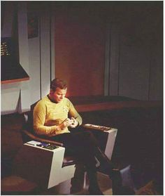 A rare, behind-the-scenes photo of William Shatner checking Facebook between takes