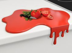 To some it may look like an overflowing spill and to others it may look like a huge pool of dripping blood, but this clever chopping board's drip is actually designed to keep it stable against the countertop.