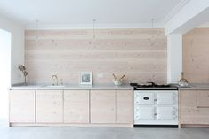 """Beautiful rose hued wood backsplash and cabinets in minimalist London kitchen. Check out the Aga range cooker. """"Wray Crescent House"""" in Islington.  Remodelista"""