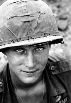 """An unidentified U.S. Army soldier wears a hand lettered """"War Is Hell"""" slogan on his helmet, in Vietnam on June 18, 1965. (AP Photo/Horst Faas)"""