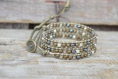 This beautiful 3x thin wrap bracelet showcases Japanese high quality TOHO 6/0 seed beads in gorgeous shades of sparkling bronze, matte soft brown, silver, and gunmetal. The beads are individually stitched carefully and securely to 1.5mm metallic shimmery bronze leather with 2 strands of a sturdy nylon beading thread that resists fraying and will not stretch. The bracelet will wrap 3 times around a wrist and has 4 button loop closures which offer ample size adjustability. It measures 20 ...