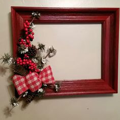 Red Barnwood type wooden frame with red & white plaid burlap ribbon, snow tipped greens & red berries. Christmas, winter, holidays