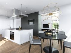 A smooth white kitchen island makes a dramatic silhouette against the textured accent wall. Black and gray define the dining space, illuminated by an intricate Hoops lamp by Giovanni Barbato. The lamp stands out even more compared to the highly minimalistic forms used throughout the rest of the space.