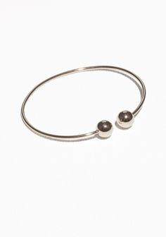 Edgy yet classy, this cuff culminates with round endcaps and has a high-shine surface.