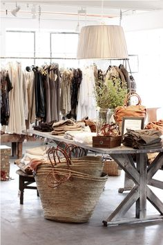 Earthy chic boutique. I like the table, floors and how the clothing is displayed on the table
