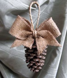 Pinecone Tassel / Ornament with burlap bow -- LOVE THIS! Easy DIY? Maybe hints of gold glitter on the pinecone? Scatter throughout the tree....