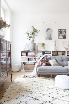 A light coloured living room with a low grey couch and a black and white kilim rug