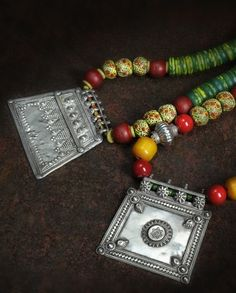 Kuchi pendants strung with Prosser beads, Krobo beads, vintage trade 'amber', seabamboo 'coral' and large green and yellow kankambas. Posted by Kim Price