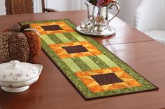 Muted greens, golds, and brown color this table runner like a field full of late summer sunflowers. Practice quick-pieced flying geese units and use strip sets for quick piecing. Digital pattern available! #FonsandPorter #TableRunner #Quilt