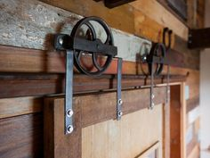 """Rustic Sliding Door """"A barn door assembly was created for only $100, using wheels affixed to brackets and a track fashioned from pieces of angle iron, new bolts and a section of metal building tension rod. The assembly was antiqued with a Plum Brown acid solution."""""""