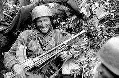Um fallschimjäger alemão sorridente com uma metralhadora Bren de fabricação inglesa capturada em Anzio, Itália, janeiro de 1944.