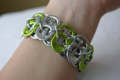A sweet and shiny cuff bracelet made out of bottle caps from soda, beer, and energy drink cans. This one of a kind bracelet features bright green accent caps. This eye-catching accessory is a fabulous Earth-happy addition to your jewelry collection!