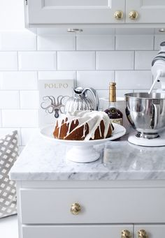 white kitchen cupboards with gold knobs and marble countertops. White subway tile backdrop.