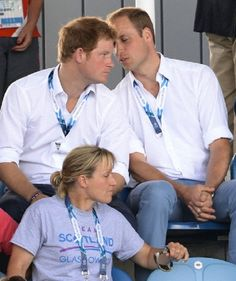 Prince William, Duke of Cambridge whispering to his brother Prince Harry as they watch a CGames Hockey match between Scotland and Wales in Scotland, UK, on the 27 July 2014