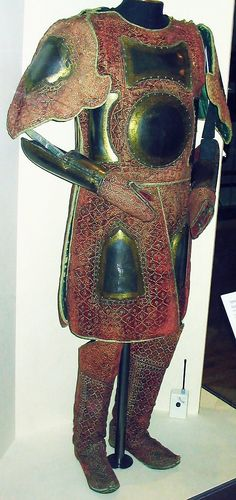 Chilta hazar masha (coat of a thousand nails), kulah khud (helmet), bazu band (arm guards) and matching boots. Indian armored clothing made from layers of fabric faced with velvet and studded with numerous small brass nails, which were often gilded. Fabric armor was very popular in India because metal became very hot under the Indian sun. This example has additional armor plates in the chest, arms and thigh area. Royal Armouries at Leeds, England.