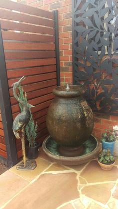 Covered the ugly hot water system using 'Screen Up' system. Stained slats in Teak. Covered toilet window using heavy duty plastic premade screen from Bunnings (Australia). Added a water feature, metal statue, coloured pots. Stone, wood, metal and water all in the one place. Still a work in progress in this pic.