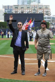 Gary Sinise Photos - Actor Gary Sinise (L) waves as he stands on the field with Marine Corps Sgt. Nick Kimmel as part of Military Opening Day before an inter-league baseball game between the Detroit Tigers and the San Diego Padres at Petco Park April 13, 2014 in San Diego, California. - Detroit Tigers v San Diego Padres