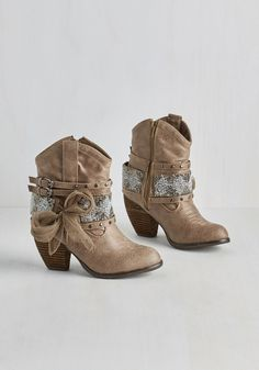 Giddy-up to grand adventures in these taupe booties! The classic cowgirl boot silhouette of this vegan faux-leather pair is boosted with stud-embellished straps, silver and gold beads, a playful mesh bow, and stacked heel for a look that shouts fun! $84.99 #grey #modcloth