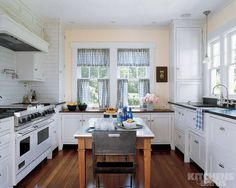 A kitchen in Delaware mixes country and city touches. The cabinets are painted a pale ivory, subway tiles are used for the backsplash, and the countertops are honed black granite. Buttercup-yellow walls, blue check curtains, and pine plank floors add rustic touches of color.   - ELLEDecor.com