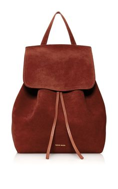 This **Mansur Gavriel** backpack is rendered in suede and features a raw interior, fold over flap and adjustable shoulder straps.