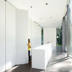 the wall of floor to ceiling storage means the kitchen clutter all disappears, and the room barely even feels like a kitchen.  Pure white and completely clean, with an incredible view through the glass walls to the lap pool outside