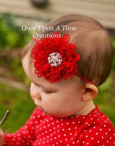 A beautiful red soft chiffon flower topped with a swirl rhinestone. Flower measures about 3.5 across and comes on a soft matching elastic
