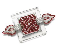 ENAMEL, ROCK CRYSTAL AND DIAMOND BROOCH, CARTIER, 1920s.   Set at the centre with an open work red enamel plaque of Chinese inspiration, within a frame of  rock crystal set between a pair of red enamel  flame motifs set with circular-cut diamonds, signed Cartier and indistinctly numbered.
