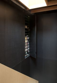 Frame House | Jonathan Tuckey Design, Holland Park, London, UK - behind the black valchromat paneling, is a bookcase located within the double-height space of the stairwell.