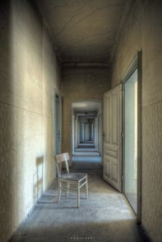 """uexplorer:  From the top floors inside an abandoned hotel, disco and soda water factory.  Abandoned a long time ago but still many things inside. Amazing place. Thought this long corridor was suitable for a classic """"chair in corridor"""" shot."""
