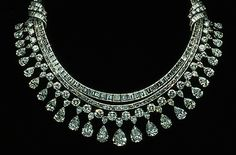 """The Hazen Diamond Necklace was designed by Harry Winston, Inc. This statement necklace is made of platinum and contains 325 diamonds that have a total weight of approximately 131.43 carats. The necklace has two sections: the upper section is a single row of emerald cut diamonds, and the lower section consists of 3-rows - a row of baguette cut diamonds and a row of round brilliant cut diamonds from which a """"fringe"""" of pear-shaped diamonds are suspended."""