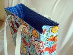 Bolsa em cartonagem e tecido 100% algodão por dentro e por fora.  Essa bolsa é ideal para carregar coisas grandes como livros, cadernos ou até mesmo umas agulhas de tricô com os novelos de lã.  Super colorida e descontraída por fora tecido Borboletas Cartoon com fundo azul turquesa e por dentro t...