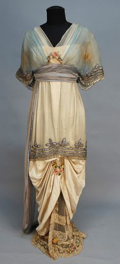 LUCILE LADY DUFF GORDON BEADED and APPLIQUED SILK GOWN, c. 1914. Cream satin having cream and blue chiffon short sleeve bodice with V-neck and back, trimmed in bands of blue satin, silver metallic cord and crystal beaded fringe and colorful silk flowers, blue satin cummerbund, hobble skirt beneath short beaded chiffon overskirt ruched in front to reveal beaded lace and chiffon underskirt and having silk flower swag, chiffon side drape studded with rhinestones. Paris label