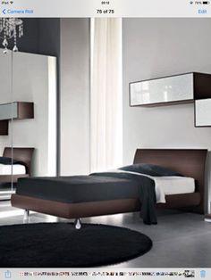 La cama es de leno y bastante grande que una cama individual. El sábana es blanca, el cobertor es negro y también la funda es negra.
