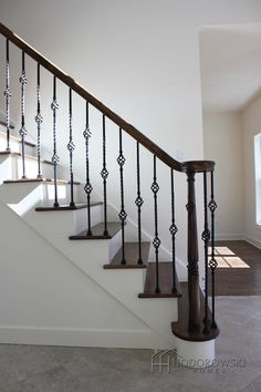 This gorgeous tiled foyer contrasts beautifully with the dark stained turned volute newel post and wrought iron spindles at our community in Twenty West. Wrought Iron Stair Spindles, Diy Stair Railing, Iron Balusters, Staircase Railings, Modern Staircase, Banisters, Staircase Design, Railing Ideas, Iron Spindle Staircase