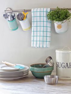 Looking for a pretty place to stash small kitchen items or herbs? Create cute, custom utensil holders with a few recycled tin cans. Spray paint and craft tape will gussy them up, and S-hooks will keep them hanging in place on a towel bar.