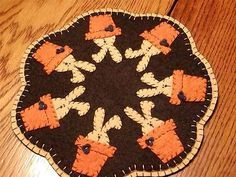 "Primitive Candle Mat - Bunny in Flower Pot 9 1/2"" dia. This is handsewn candle mat. The tea dyed backing has a blanket stitch to a black top. Each bunny is hand cut and hand sewn in a flower pot. Enjo"