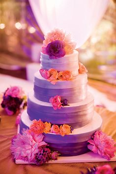 bright purple, lavendar wedding cake with fresh pink flowers and orange roses