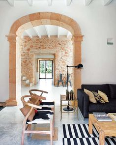 This freshly renovated former oil mill owned by an architect, dates back to the 1700's and is located in Mallorca, Spain. (Never seen a pair of Wegner Y-chairs with cowhide seats before!)