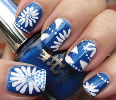 White flower art atop a shimmery blue - this always works as a great base to showcase a lot of good nail art.
