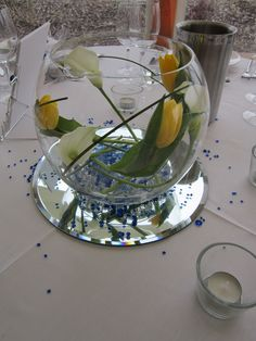 Goldfish bowl vases with white calla lilies and yellow tulips wrapped inside for a simple but striking wedding table center .