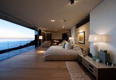 chambre cocooning au design moderne avec lit double en cuir beige, meubles en bois massif et vue sur la mer