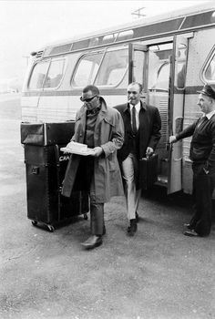 Ray Charles, protecting his chess board, during a transfer from his tour bus to his tour plane, on the tarmac of an LA airport, on May 3, 1966 (with Joe Adams). Photo by Bill Ray.