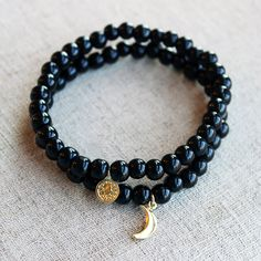Two stretchy bracelets featuring Jet beads + gold vermeil charms (a coin + a crescent moon). $25 for the set