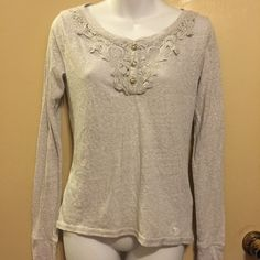 A gray Abercrombie & Finch  top A pull over top with  three buttons up in front of top . The. Top also has a crochet design in front and band on end of sleeves and high front and low back Abercrombie & Fitch Tops
