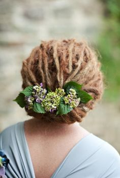 Shoulder length dreads softly clustered in a low wide chignon dressed with hydrangea buds - Hair by jac